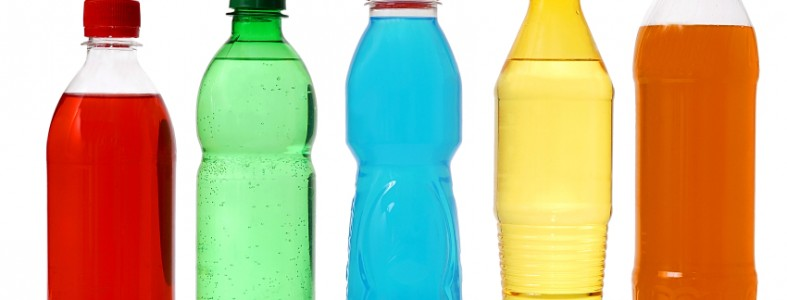 five colored bottles with juice and soda