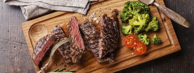 Sliced medium rare grilled Beef steak Ribeye with broccoli on cu